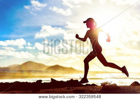 Running fitness girl jogging through landscape beach background at sunset sprinting with speed and motivation. Summer workout athlete runner. Fit body silhouette outdoor training cardio.