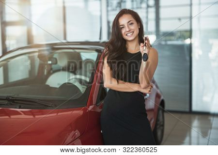 Young Beautiful Woman Looks Happy With Car Keys In Her Hand Standing In Dealership Center Buying Bra