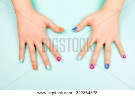 Womans Hands With Perfect Manicure In Trendy Neon Colors On Turquoise Background. Beauty Concept.