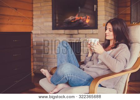 Young Beautiful Woman Relaxing With Cup Of Herbal Tea Near Fireplace In Cozy Wooden House.