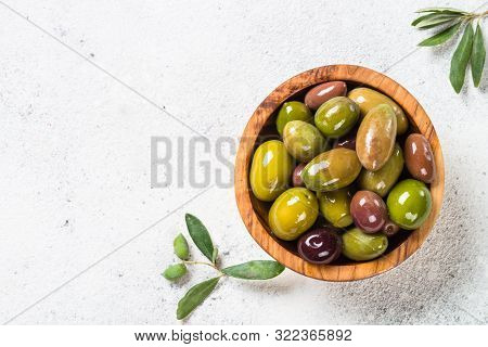 Olives In Wooden Bowl On White Stone Background. Top View With Copy Space.