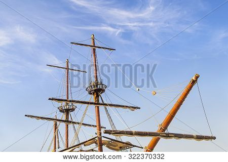 Masts, Sail Yards With The Lowered Sails And Rigging Of A Sailing Ship Against A Clear Blue Sky With