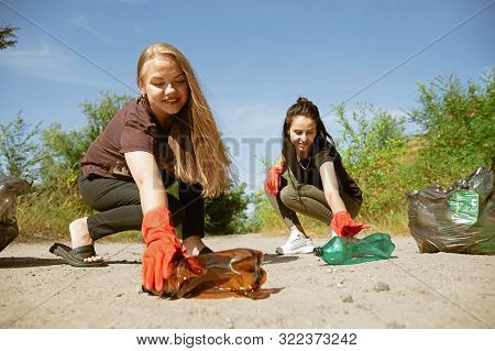 Clean Our Home Together. Group Of Volunteers Tidying Up Rubbish On Beach In Sunny Day. Young Women T