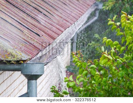 Heavy Rain. Rainwater Pouring Out Of Old Gutter