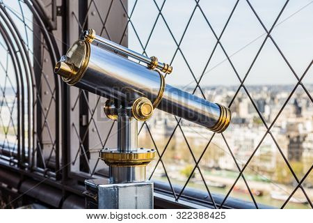 Paris, France, March 30, 2017: Eiffel Tower telescope overlooking for Paris. Old panoramic viewer or telescope on the eiffel tower top. Monocular telescope at Eiffel Tower and view over the city