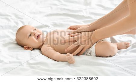 Colics Prevention. Mother Massaging Tummy Of Cute Newborn Baby In Bed, Panorama