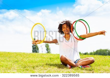 Young Girl With Curly Hair Rotate Hoops In Hands
