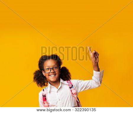 Look Up. Cheerful Black Schoolgirl Pointing Finger Upward Having Question Or Idea On Yellow Studio B