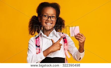 Cute Black Elementary Student Girl Pointing Finger At Blank Paper Card Over Yellow Studio Background