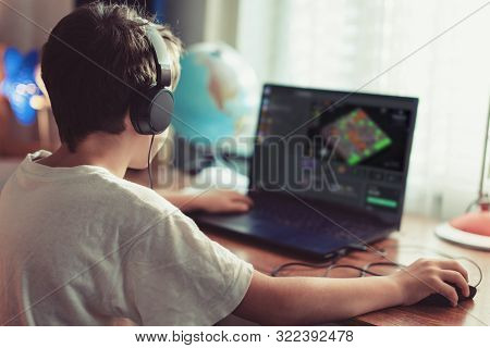 Little Dependent Gamer Boy Playing Mass Multiplayer Game On Laptop At Home