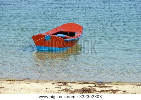 Wooden Fishing Boat Moored On The Shore.