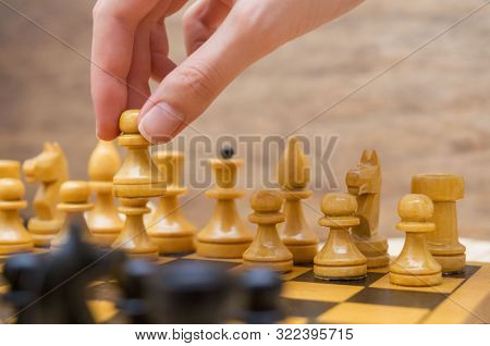 Girl Makes A Move White A Pawn On A Chessboard