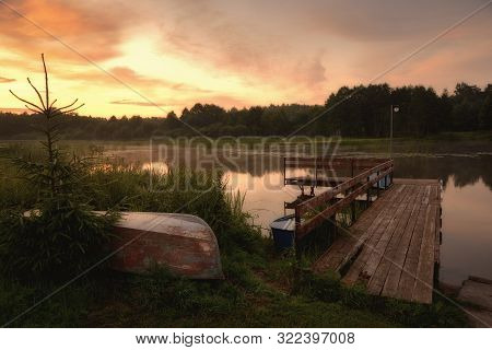 Summer Sunset On A Forested River With Inverted Boats And A Old Wooden Pier