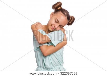 Self love and self care. Portrait of teen girl Hugging oneself, isolated on white background. Cute caucasian young teenager smiling with eyes closed. Happy funny child.