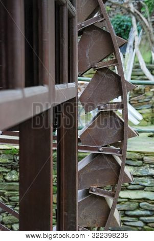 Close Up Of Old Metal Water Wheel At An Old Grist Mill.