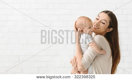Cheerful Mother Cuddling Her Newborn Son At Home, Enjoying Time Together, Panorama With Copy Space