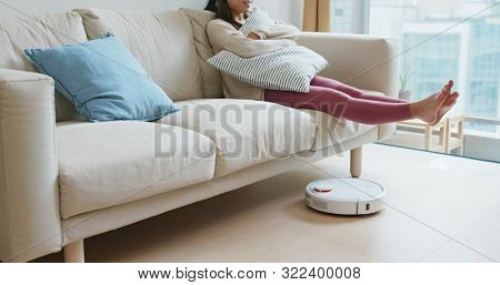 Woman lift up the feet with robotic vacuum on the floor at home