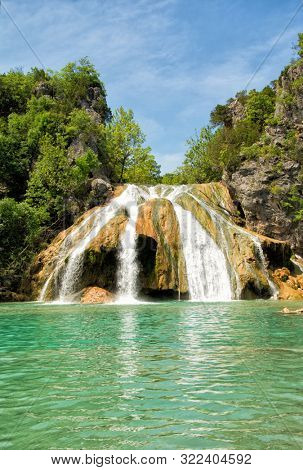 Waterfall at Turner Falls, Oklahoma, with beautiful aqua colored water under blue spring sky