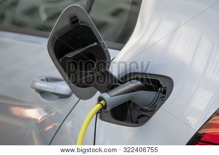 Electric Car Silver Color - Plugged In For Charging. Charging Station For Electric Car. Close Up Of
