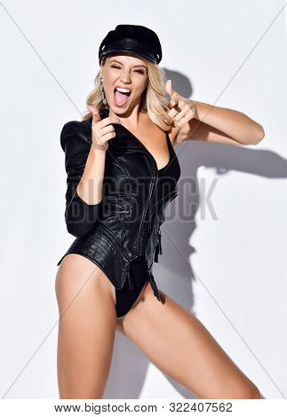 Brutal Blonde Woman Fashion Rebel Trendsetter In Black Bodysuit, Modern Leather Jacket And Cap Is Po
