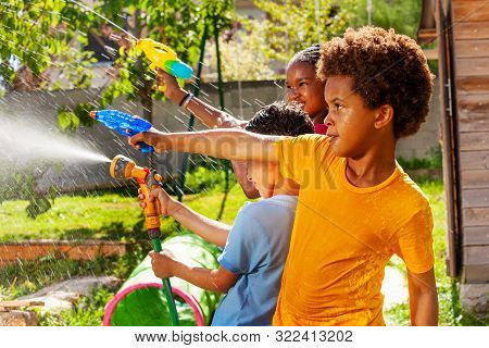 Boy With Group Of Children Shoot Water Pistol