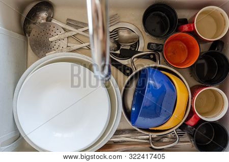 Dirty Dishes In A Ceramic Kitchen Sink. Unwashed Plates, Mugs And Cutlery. Top View