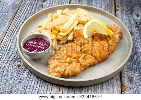 Fried Wiener schnitzel from veal topside with French fries and cranberry sauce as closeup modern design plate