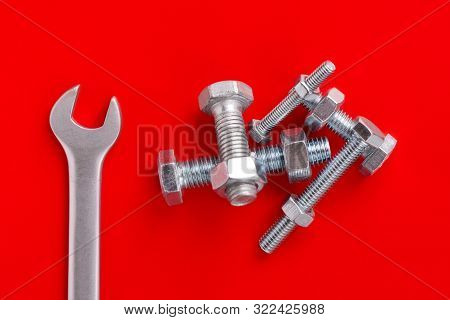 Wrench And Bolts With Nuts Close-up On A Red Background. A Bunch Of Bolts And Nuts. Bolts, Nuts And