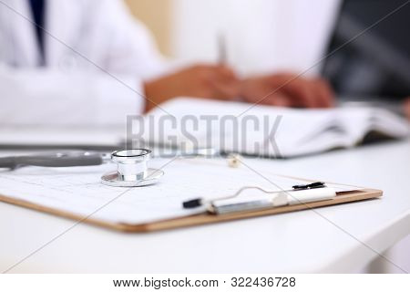 Stethoscope Head Lying On Medical Forms Closeup While Medicine Doctor Working In Background. Patient