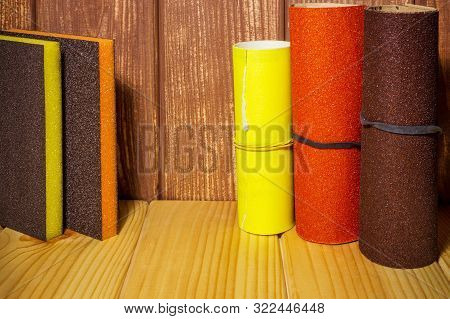 Set of abrasive tools and sandpaper on brown vintage wood background poster
