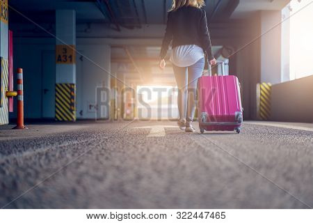 Photo From Back Of Blonde With Pink Suitcase Walking Along Passage At Airport, Blurred Background. L