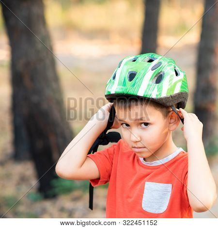 A Boy Puts A Green Helmet On His Head.