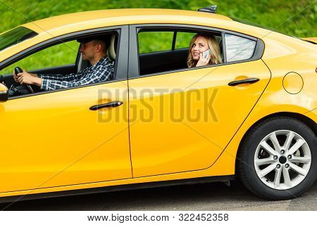 Photo Of Young Woman Talking On Phone While Sitting In Back Seat Of Yellow Taxi With Driver In Summe