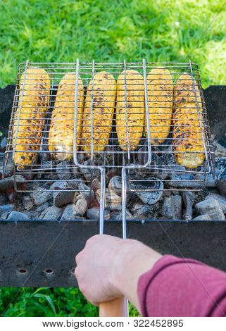 Cook's Hand Flips The Grill With Ears Of Corn For Grilling On Charcoal