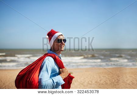 Christmas, Holidays, Travel And People Concept - Man In Santa Claus Hat With Gift Box Over Tropical