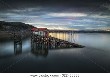 Sunset And A Calm Evening Tide At The Old Lifeboat Station On Mumbles Pier, Swansea Bay, South Wales
