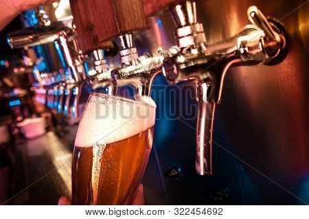 Bartender Pouring A Large Lager Beer In Tap. Bright And Modern Neon Light, Males Hands. Pouring Beer