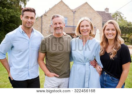 Portrait Of Family With Senior Parents And Adult Offspring Walking And Talking In Garden Together