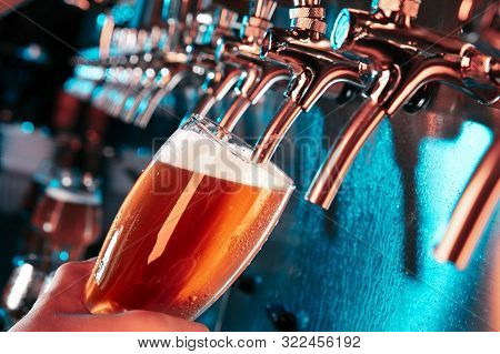 Hand Of Bartender Pouring A Large Lager Beer In Tap. Bright And Modern Neon Light, Males Hands. Pour