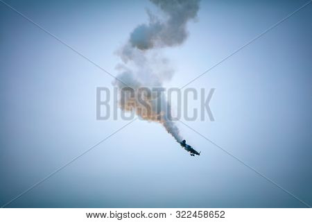 Airplane falling down with smoke getting from engine. Airshow performance.