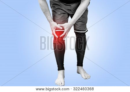 Muscle Man Holds His Injured Knee On Blue Background. Red Color Is Pain.