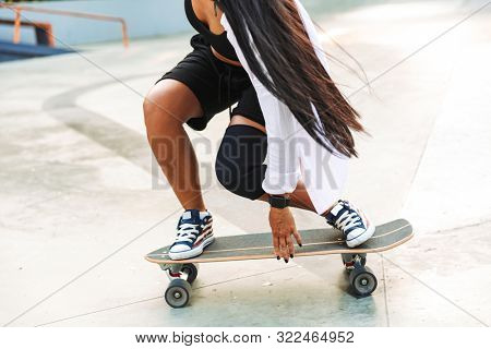 Cropped photo of caucasian young woman in streetwear riding skateboard in skate park