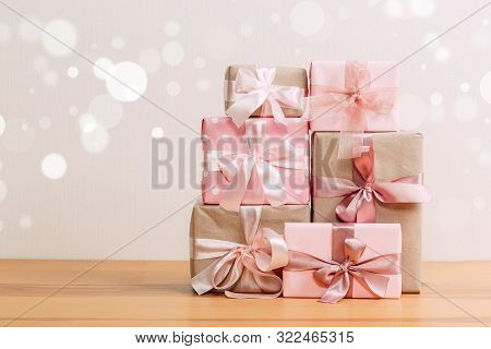 Set Of Beautiful Different Gift Boxes Made By Handmade With Pink Bows On A Wooden Table With A Light