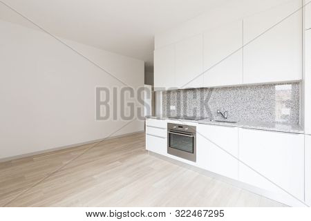 Large empty room with white walls and modern kitchen. Nobody inside