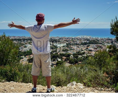 Tourist Guy Stands On A Hilltop Spreading His Arms Wide To The Side, Travel Concept, Freedom