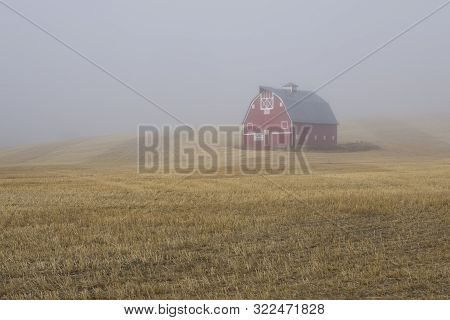 A Red Barn Shrouded By Fog Stands On The Palouse Reagion Of Eastern Washington.