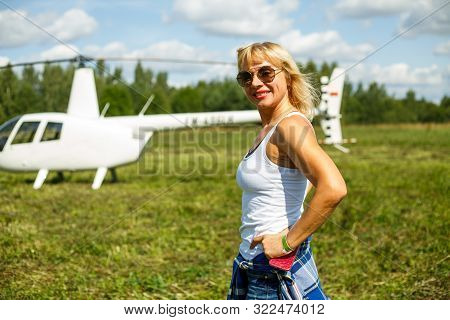 Portrait Of A Beautiful Tanned Mature Caucasian Woman In A White T-shirt, Sunglasses And Short Jeans