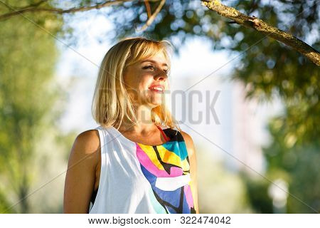 Portrait Of A Beautiful Tanned Mature Caucasian Woman In A T-shirt Under A Tree Branch On A Sunny Su