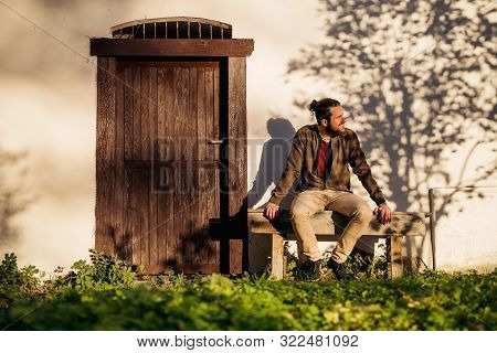 Lonely Young Man Sitting On Bench In Front Of Old House.