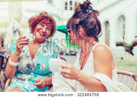Two Smiling Senior Women Talking And Drinking Coffee While Looking Each Other In A Outdoor Cafe